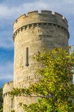The conical stone tower of the castle. Against the background of the blue sky and green trees stock photos