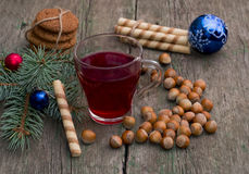 Coniferous branch with Christmas tree decorations, tea, sweets a Royalty Free Stock Photos