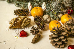 Coniferous branch with different pine cones,tangerines. With red hearts on light table Royalty Free Stock Images