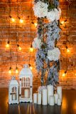 Coniferous branches with hydrangea bushes, candles and light bulbs on a brick background, vertical frame royalty free stock images