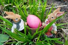 Conigli che portano l'uovo di Pasqua su fondo e sul segno verdi Fotografia Stock