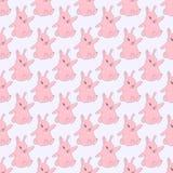 Conigli rosa che si siedono su un fondo blu solido Fotografie Stock