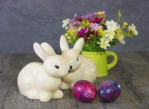Conigli, uova e fiori della decorazione di Pasqua Immagini Stock