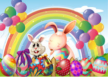 Coniglietti ed uova variopinte vicino all'arcobaleno ed ai palloni di galleggiamento Fotografia Stock Libera da Diritti