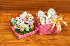 Coniglietto bianco dei biscotti di Pasqua ed uova colorate in contenitori di regalo Fotografia Stock