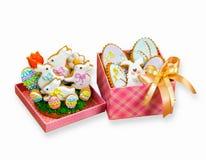 Coniglietto bianco dei biscotti di Pasqua ed uova colorate in contenitori di regalo Immagine Stock
