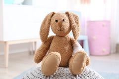 Coniglietto del giocattolo con il cuscinetto bendato sul pouf all'interno fotografia stock