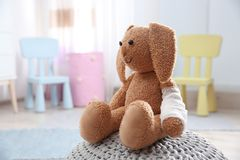 Coniglietto del giocattolo con il cuscinetto bendato sul pouf, spazio per testo Medico del ` s dei bambini immagini stock