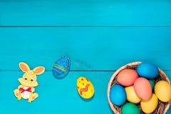 Coniglietto di pasqua accanto alle uova di Pasqua su un fondo di legno blu Fotografie Stock Libere da Diritti