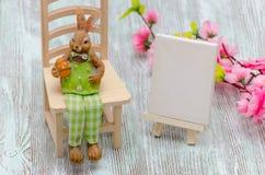 Coniglietto di pasqua che si siede sul panchetto con un uovo, un cavalletto di verniciatura ed i fiori sopra fondo di legno Immagini Stock Libere da Diritti