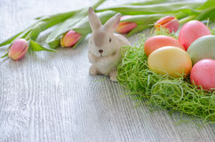 Coniglietto di pasqua con i tulipani, il nido e le uova sul vntage di legno Fotografia Stock