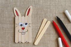 Coniglietto di pasqua di divertimento fatto dei bastoni e dei pennarelli di legno su tela approssimativa fotografia stock libera da diritti
