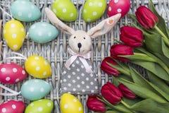 Coniglietto di pasqua, tulipani rossi, uova tinte colorate su fondo di vimini Fotografie Stock