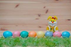 Coniglietto felice con le uova di Pasqua e l'erba sul Fotografia Stock