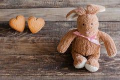 Coniglietto lanuginoso del giocattolo con i biscotti sotto forma dei cuori cartolina Fotografia Stock