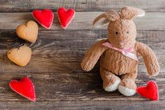Coniglietto lanuginoso del giocattolo con i cuori del feltro ed i biscotti sotto forma di He Fotografia Stock