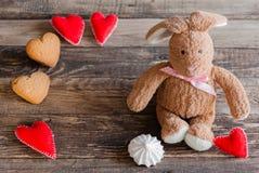 Coniglietto lanuginoso del giocattolo con i cuori del feltro ed i biscotti sotto forma di He Fotografie Stock Libere da Diritti