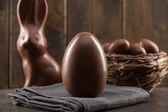 Coniglietto, uova e dolci di pasqua del cioccolato su fondo rustico fotografia stock libera da diritti