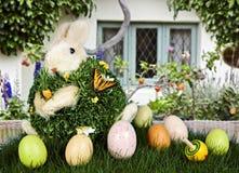 Coniglio & uova di Pasqua in erba verde con il cottage Immagine Stock