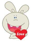 Coniglio che ride e che tiene un cuore rosso Fotografia Stock Libera da Diritti
