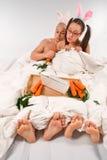 Coniglio che si trova a letto con il computer portatile Immagine Stock