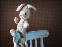 Coniglio d'annata del giocattolo La vecchia lepre molle d'annata del giocattolo si siede in vecchia sedia bianca fotografia stock