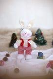 Coniglio del giocattolo di Natale sugli alberi del fondo Immagine Stock