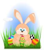 Coniglio di pasqua del fumetto su erba che tiene un uovo di Pasqua Illustrazione Vettoriale