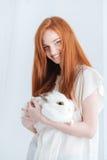 Coniglio sorridente della tenuta della donna della testarossa Fotografia Stock