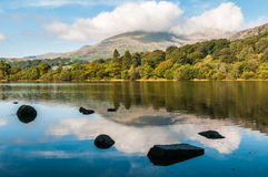 Coniston Water in the English Lake District. An early morning view of Coniston Water in the English Lake District. The summit of Coniston Old Man in the Royalty Free Stock Images