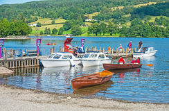 Coniston Water. Jetty on Coniston Water in the English Lake district showing boats for hire. Distant fields and woods. Popular holiday and tourist destination stock photography