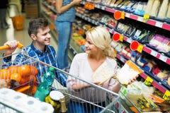 Coniugi positivi felici che comprano cheddar nella sezione del formaggio Fotografia Stock Libera da Diritti