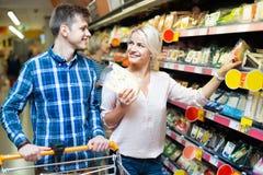 Coniugi positivi felici che comprano cheddar nella sezione del formaggio Fotografia Stock