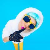 Conjeture a la muchacha de la moda en una sudadera con capucha blanca en un fondo azul Winte Imagenes de archivo
