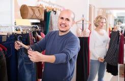 Conjoints achetant des paires de jeans classiques dans la boutique Photos stock