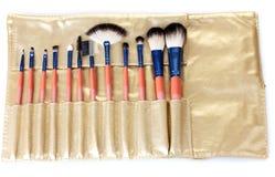 Conjunto de cepillos del maquillaje en caja de cuero de oro Imagen de archivo