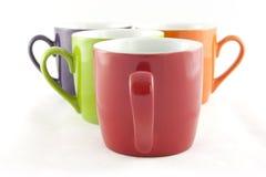 Conjunto de cuatro tazas del color aisladas en blanco Imágenes de archivo libres de regalías