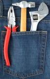 Conjunto de ferramentas no bolso das calças de brim Fotografia de Stock Royalty Free