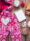 Conjunto de la Navidad Manta caliente, suéter, vela, cuaderno, especias, canela, conos del pino, corazón en el fondo de madera Fotos de archivo libres de regalías