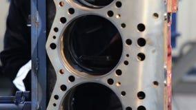 Conjunto de motor O trabalhador limpa o motor O trabalhador limpa os cilindros do motor antes do conjunto Bloco de motor diesel video estoque