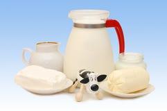 Conjunto de productos lácteos y de una vaca del juguete imagenes de archivo