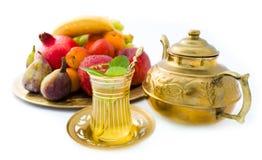 Conjunto de té oriental con las frutas en la placa de oro Fotografía de archivo