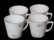 Conjunto de tazas blancas aisladas en negro Fotos de archivo