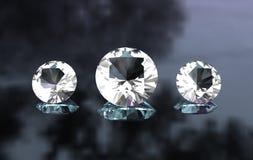 Conjunto de tres diamantes redondos en superficie brillante Foto de archivo