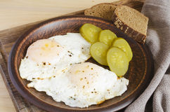 Conjunto del desayuno De huevos fritos con pan adobado del pepino y de centeno Estilo rústico fotografía de archivo