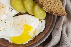 Conjunto del desayuno De huevos fritos con pan adobado del pepino y de centeno Estilo rústico imagen de archivo libre de regalías