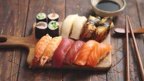 Conjunto del sushi Diferentes tipos de rollos de sushi en tablero de servicio de madera almacen de metraje de vídeo