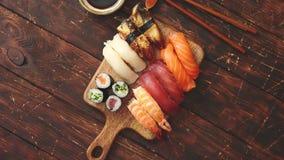 Conjunto del sushi Diferentes tipos de rollos de sushi en tablero de servicio de madera metrajes