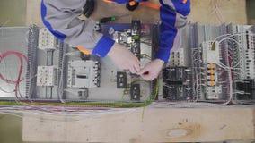 Conjunto elétrico do armário da fábrica usando uma chave de fenda da mão na fábrica filme