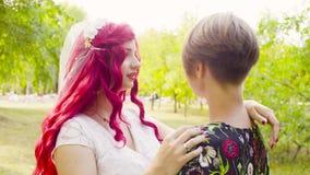 Conjunto nupcial doble en las rosas blancas La novia y el novio se están abrazando y hablar metrajes